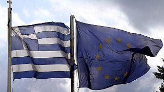 Οι σημαίες της Ελλάδας και της Ευρωπαϊκής Ένωσης ανεμίζουν με φόντο τον αττικό ουρανό.