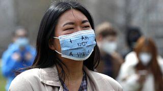 """شابة ذات ملامح آسيوية تلبس كمامة كتب عليها """"لست فيروساً"""""""