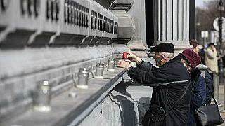 Anziani accendono candele al muro degli eroi fuori dal museo della Casa del Terrore, a Budapest, in occasione del giorno della memoria delle vittime del comunismo