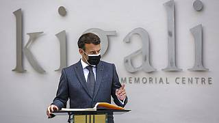 French President Emmanuel Macron speaks next to the visitor's book at the genocide memorial site in the capital Kigali, Rwanda