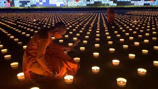 Buddhist monks light candles on Visakha Bucha Day