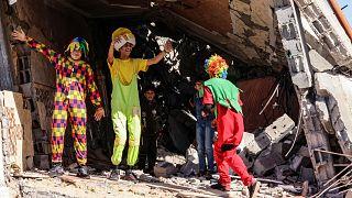 فلسطينيون يرتدون زي المهرجين يستمتعون بالأطفال وسط أنقاض مبنى دمر خلال القصف الإسرائيلي الأخير في رفح ، جنوب قطاع غزة