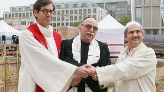 """القس غريغور هوبرغ، الحاخام أندرياس ناخاما والإمام قادر سنجي يقفون خلال حفل وضع حجر الأساس للمبنى متعدد الأديان """"البيت الواحد""""  برلين ألمانيا."""