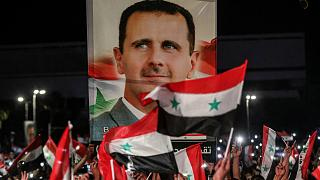 سوريون يلوحون بالأعلام الوطنية ويحملون صورة كبيرة لرئيسهم وهم يحتفلون في شوارع العاصمة دمشق.