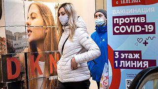 Frau vor Impfplakat in Moskau