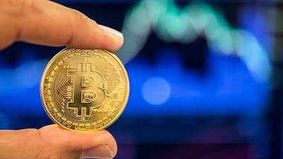 """A person holds a visual representation of the digital cryptocurrency Bitcoin, at the """"Bitcoin Change"""" shop in the Israeli city of Tel Aviv."""