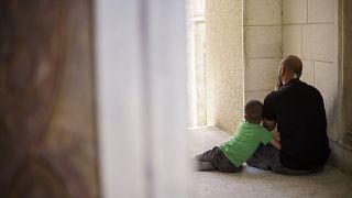 Un bambino palestinese abbraccia il padre