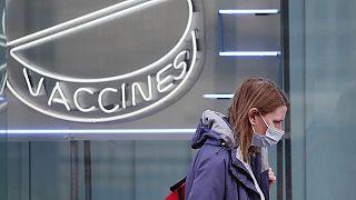Eine Frau mit Maske läuft an einem Neon-Schriftzug des Wellcome Institutes vorbei, 02.02.2021