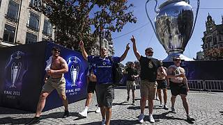 Chelsea supporters walk past a giant replica of the Champions League trophy in downtown Porto
