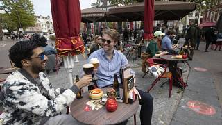 In this Wednesday, April 28, 2021 file photo, people toast after terraces reopened at midday as the Netherlands began cautiously relaxing restrictions.