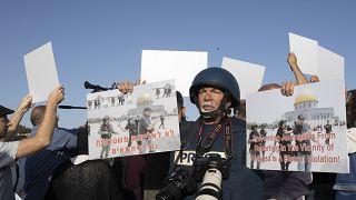 صحفي يحمل لافتة تدين الانتهاكات بحق الصحفيين الفلسطينين في حي الشيخ جراح، القدس.