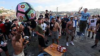 Manchester City supporters drink and chant by the Douro river bank in Porto, Portugal, Friday, May 28, 2021.