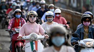مواطنون فيتناميون يضعون كامات على وجوههم وهم على دراجاتهم في طريقهم إلى العمل وسط العاصمة هانوي