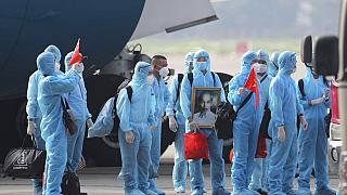 Vietnamese COVID-19 patients in protective gear arrive at Noi Bai airport in Hanoi, Vietnam, in July 2020.
