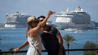 زوجان يلتقطان صورة سيلفي في ميناء مدينة ميورقة الإسبانية وخلفهما سفنٌ سياحية راسية
