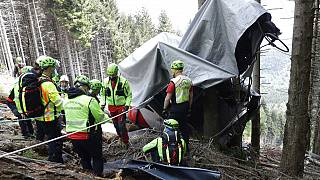Rescuers search for evidence in the wreckage near the summit of the Stresa-Mottarone line in Piedmont on Wednesday