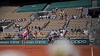 A romena Patricia Maria Tig serve perante o público no duelo contra a japonesa Naomi Osaka