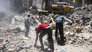 Heavy machinery sifts through the rubble of a destroyed building in Gaza for valuables on Thursday, May 27