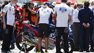 Teammates of 19 years-old Swiss racer Jason Dupasquier by his motorbike during a minute's silence on Sunday