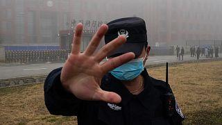 Egy biztonsági tartja távol az újságírókat a Vuhani Virológiai Intézet előtt