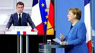 French President Emmanuel Macron is seen on a video screen during a joint press conference with German Chancellor Angela Merkel