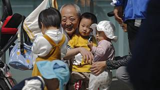 An elderly man plays with children near a commercial office building in Beijing on May 10, 2021.