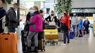 Travellers stand in an airport in the Netherlands