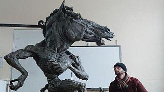 lo scultore Aidan Harte con la sua opera