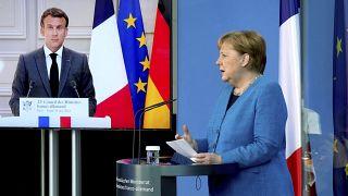 الرئيس الفرنسي إيمانويل ماكرون يظهر على شاشة فيديو خلال مؤتمر صحفي مشترك مع المستشارة الألمانية أنغيلا ميركل.