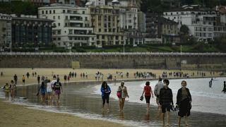 أشخاص يسيرون على طول شاطئ لا كونشا، بعد رفع قيود الإغلاق ، في سان سيباستيان ، شمال إسبانيا ، الأحد 9 مايو 2021.