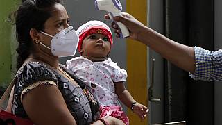 Un sanitario toma la temperatura a una mujer en Bombay, India