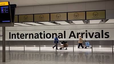 Arriving passengers walk past a sign in the arrivals area at Heathrow Airport in London, on Jan. 26, 2021.