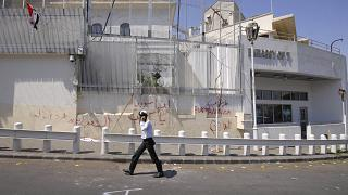 FILE: A policeman walks in front of the damaged US embassy after pro-government protesters attacked the embassy in Damascus, Syria, 2011