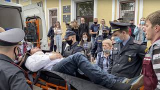Police officers and paramedics carry Stsiapan Latypau, a Belarusian activist who attempted to kill himself during a court hearing in Minsk, Belarus, Tuesday, June 1, 2021