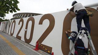 Munkások dekorálják a tokiói új Nemzeti Stadion körüli kerítést Tokióban 2021. június 1-jén.