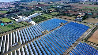 Flugzeug überfliegt ein Feld mit Solaranlagen