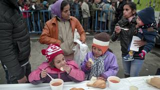 FILE - In this Wednesday, Dec. 16, 2015 file photo, homeless children eat as others wait in line for their turn outside the main railway station in Bucharest, Romania.