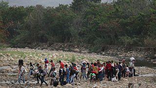 Ülkelerindeki sosyal ve ekonomik krizden kaçan Venezuelalılar, Tachira Nehri'ni kullanarak Kolombiya'ya kaçarken (27 Şubat 2019)