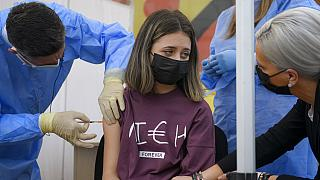 FILE Photo: A girl gets a Pfizer BioNTech COVID-19 vaccine in Bucharest, Romania, Wednesday, June 2, 2021.