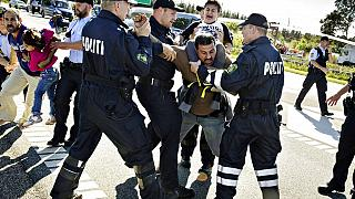 In this Sept. 9, 2015 file picture police grab a refugee as hundreds of refugees walk in Southern Jutland motorway near Padborg in Denmark