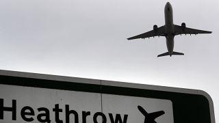 Heathrow Havaalanı tabelası üzerinden geçen bir yolcu uçağı