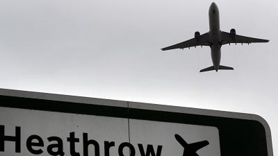 A plane takes off over a road sign near Heathrow Airport in London.