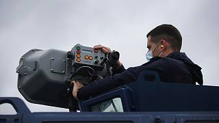 Police officer Dimitris Bistinas operates a long range acoustic device attached on a police vehicle along the Greek-Turkish border near the town of Feres May 21, 2021.