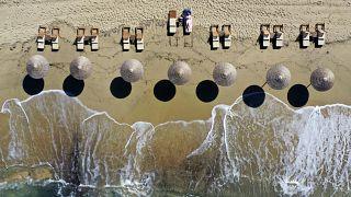Une femme profite du soleil sur la plage de Plaka sur l'île de Naxos, en Grèce, vendredi 14 mai 2021.
