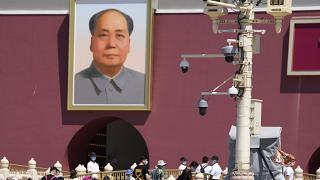 With surveillance cameras seen on a pole, plainclothes security personnel watch as tourists visits Tiananmen Gate on the 32nd anniversary of a deadly crackdown on protest.