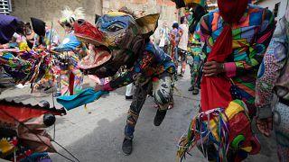 Personas vestidas con trajes de diablo celebran la fiesta católica del Corpus Christi en Naiguatá, Vargas, Venezuela, el 3 de junio de 2021.