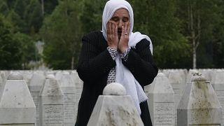 Munira Subasic who lost her son and the husband in Srebrenica massacre prays at the memorial cemetery in Potocari near Srebrenica, Bosnia, Friday, May 28, 2021.