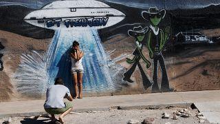 يلتقط الزوار صورًا أمام لوحة جدارية تصور سفينة فضاء خارج مركز فراش جارك في هيكو نيفادا.