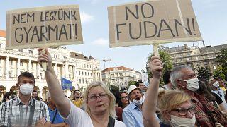 """Los manifestantes sostienen pancartas en las que se lee en húngaro """"no seremos una colonia"""", a la izquierda, y """"no Fudan"""" en Budapest, Hungría, el 5 de junio de 2021."""