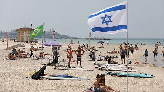 Tavaly májusi fotó: emberek napoznak és sétálnak egy tengerparti strandon Tel-Avivban